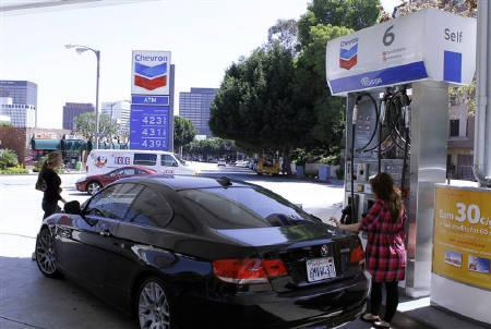 A woman stands at a petrol pump at a Chevron gasoline station in Los Angeles,California April 11, 2011. REUTERS/Fred Prouser/Files