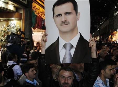 A supporter of Syria's President Bashar al-Assad holds aloft a photograph of the president at Hamidiya market in Damascus April 30, 2011. REUTERS/Khaled al-Hariri