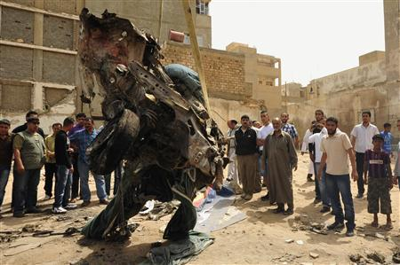 Libyans watch as the remains of a car, which had exploded near a courthouse, is removed from the scene in Benghazi, May 4, 2011. The car blew up in the eastern rebel stronghold of Benghazi on Tuesday, residents said. REUTERS/Esam al-Fetori