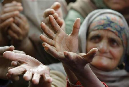 A devotee raises her hands to receive food from a roadside charitable community kitchen, on the outskirts of Jammu January 16, 2011.  REUTERS/Mukesh Gupta/Files