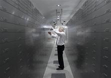 <p>Сотрудник банка в Вене достает депозитную ячейку, 21 июля 2009 года. Власти Австрии заморозили средства на сумму около 1,2 миллиарда евро, которые предположительно принадлежат ближнему окружению ливийского лидера Муаммара Каддафи, сообщил в среду Рейтер высокопоставленный представитель австрийского Центробанка. REUTERS/Heinz-Peter Bader</p>