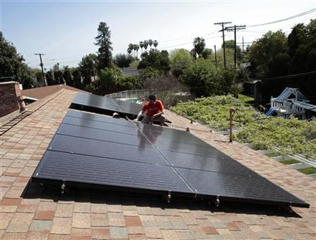 Mike Jones stands next to solar panels on the roof of his home in Los Angeles, California March 18, 2011. REUTERS/Lucy Nicholson