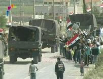 <p>People hold Syrian flags by the side of the road as Syrian military vehicles leave Deraa May 5, 2011 in this still image taken from video. REUTERS/Syrian TV via Reuters TV</p>