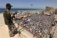 <p>Un combatiente rebelde monta guardia durante las plegarias del viernes en Bengasi, mayo 6, 2011. REUTERS/Mohammed Salem</p>