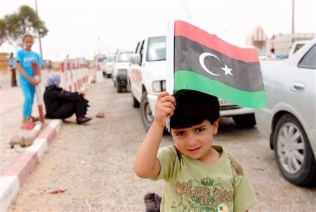 A Libyan boy holds up a Kingdom of Libya flag at a checkpoint after crossing from Libya into Tunisia at the border crossing in Dehiba May 7, 2011. REUTERS/Anis Mili