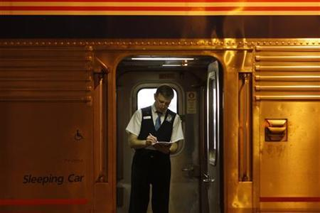 An Amtrak train attendant looks over paperwork on the 5 California Zephyr train in Chicago June 12, 2008. REUTERS/Joshua Lott