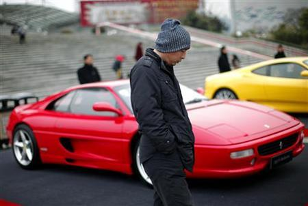 A man walks past a Ferrari 355 F1 Berlinetta during an exhibition held to celebrate Ferrari's 999th car sold in China from 2004 to 2010, at the Oriental Pearl Tower in Shanghai January 14, 2011. REUTERS/Carlos Barria