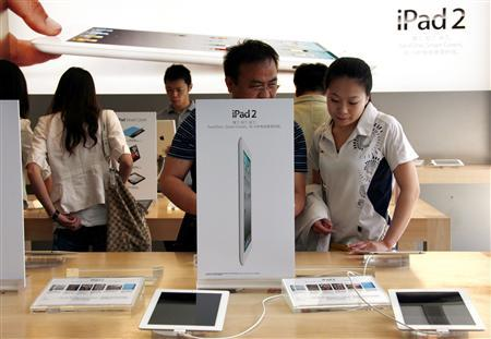 Customers look at various iPad 2 products during the China launch at an Apple Store in central Beijing May 6, 2011. REUTERS/David Gray