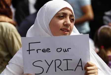 A girl holds a poster as she takes part in a demonstration against the Assad government outside the Syrian embassy in London, May 7, 2011. REUTERS/Andrew Winning