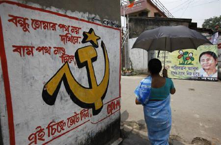 A woman carrying an umbrella walks past political murals and posters in Kalighat district, the neighbourhood where Trinamool Congress leader Mamata Banerjee lives, in Kolkata May 12, 2011. REUTERS/Danish Siddiqui