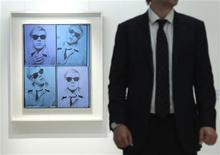 Funcionário da Christie's posa para foto ao lado do primeiro autorretrato de Andy Warhol, em Londres. 15/04/2011 REUTERS/Luke MacGregor
