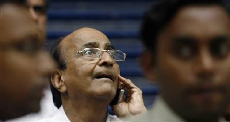 A man speaks on a phone as he looks at a large screen displaying India's benchmark share index on the facade of the Bombay Stock Exchange (BSE) building in Mumbai July 31, 2009. REUTERS/Punit Paranjpe/Files