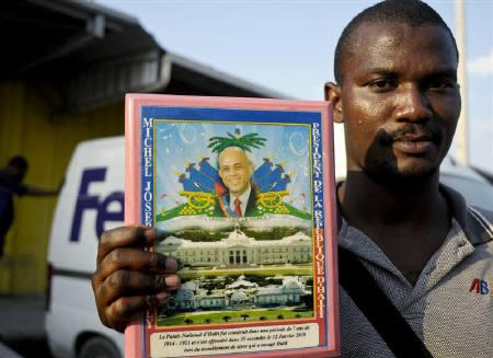A supporter waiting for the return of President-elect Michel Martelly holds a plaque bearing his likeness outside the airport in Port-au-Prince April 25, 2011. REUTERS/Swoan Parker/Files