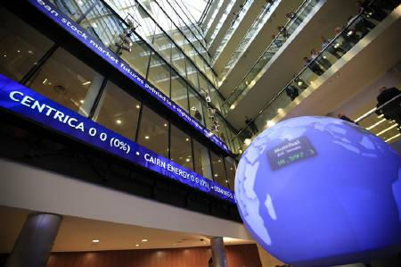 Workers look into the atrium as financial data and news headlines stream accross ticker screens at the London Stock Exchange after Britain's Chancellor of the Exchequer George Osborne inaugurated the ceremonial market opening in the City of London, May 10, 2011.  REUTERS/Andrew Winning