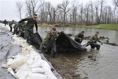 <p>Members of the Princess Patricia's Canadian Light Infantry (PPCLI) work at shoring up a dike along the Assiniboine River near Poplar Point, Manitoba, May 13, 2011. REUTERS/Fred Greenslade</p>