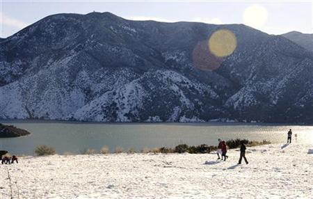People walk in the snow at Pyramid Lake in the Angeles National Forest in the ''Grapevine'' area of Interstate 5 (I-5), north of Los Angeles January 3, 2011. REUTERS/Gene Blevins