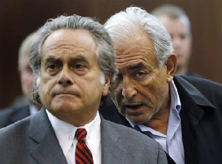 International Monetary Fund (IMF) chief Dominique Strauss-Kahn (R) talks with his lawyer Benjamin Brafman during his arraignment in Manhattan Criminal Court in New York May 16, 2011. REUTERS/Shannon Stapleton/Files