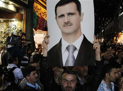 EDITOR'S NOTE: PICTURE TAKEN ON GUIDED GOVERNMENT TOUR A supporter of Syria's President Bashar al-Assad holds aloft a photograph of the president at Hamidiya market in Damascus April 30, 2011. REUTERS/Khaled al-Hariri