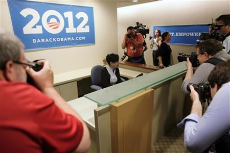 Volunteer receptionist Hattie Hester answers the phone while surrounded by photographers as they toured President Barack Obama's new campaign headquarters in Chicago May 12, 2011. REUTERS/John Gress