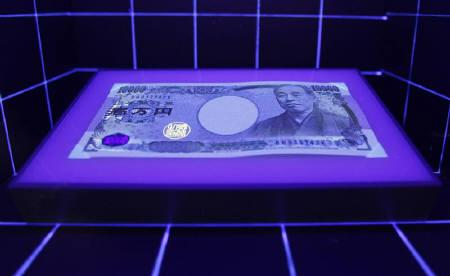 A 10,000 Yen banknote is displayed under a light to demonstrate how it differs from a forgery at the currency museum of the Bank of Japan in Tokyo October 6, 2010. REUTERS/Kim Kyung-Hoon/Files