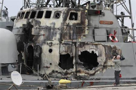 EDITOR'S NOTE: PICTURE TAKEN ON GUIDED GOVERNMENT TOURA cameraman works near destroyed Libyan warships at the sea port in Tripoli May 20, 2011. REUTERS/Louafi Larbi