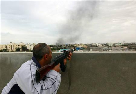 A rebel fighter takes cover atop a building during a firefight and shelling near Tripoli street in Misrata April 21, 2011. REUTERS/Yannis Behrakis/Files