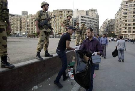 Soldiers stand guard while men clean Tahrir Square in Cairo April 12, 2011. REUTERS/Asmaa Waguih/Files