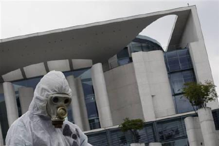 A ''Tollwood'' environmental activist wearing protective gear protests against the government's nuclear energy policy calling for a swift nuclear energy exit outside the Chancellery in Berlin May 16, 2011.  REUTERS/Thomas Peter