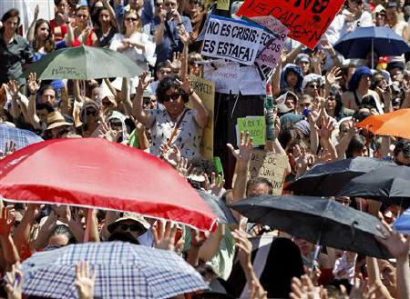 Demonstrators raise their hands in approval during an assembly to vote on whether to continue their campout in Madrid's Puerta del Sol May 22, 2011. REUTERS/Paul Hanna