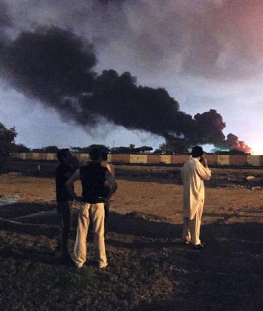 Men watch as a plume of smoke rises from the Mehran naval aviation base after it was attacked by militants in Karachi May 22, 2011. REUTERS/Athar Hussain