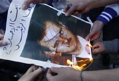 Syrians living in Greece set fire to a poster of Syrian President Bashar al-Assad, in solidarity with anti-government protesters in Syria, outside the Syrian embassy in Athens, May 6, 2011. The EU imposed sanctions on Assad and other senior officials on Monday. REUTERS/John Kolesidis