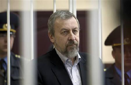 Former presidential candidate Andrei Sannikov stands in a guarded cage during a court hearing in Minsk May 14, 2011. REUTERS/Julia Darashkevich