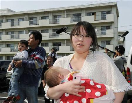 A woman evacuee from Iitate village carries a baby, as she arrives at a evacuation center in Fukushima, located about 40 kilometres (24 miles) from the tsunami-crippled Daiichi nuclear power plant and is included in an expanded evacuation zone, May 15, 2011. REUTERS/Kyodo