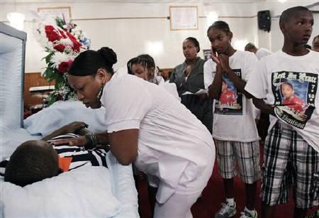 Mourners pay their respects at the coffin of Tyquan Jamison in the Brooklyn borough of New York July 26, 2010. Jamison, 15, was murdered after a dispute at a basketball court in the Brownsville section of Brooklyn on July 19. REUTERS/Shannon Stapleton/Files