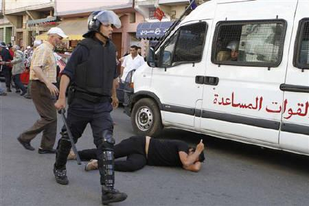 A Moroccan riot policeman walks past a protester lying on the ground during a demonstration organized by the February 20 anti-government movement demanding political reforms, in Casablanca May 22, 2011. REUTERS/Stringer