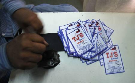 An inmate stamps labels that will be used in the packaging of baked products inside the Tihar Jail complex in New Delhi May 11, 2011. REUTERS/Adnan Abidi