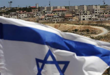 An Israeli flag waves on a hill near the West Bank Jewish settlement of Elazar, in the Etzion settlement bloc near Bethlehem May 22, 2011. REUTERS/Ronen Zvulun