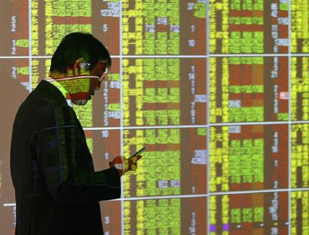 A man uses his mobile phone as he walks past a stock exchange board inside a bank in Taipei March 10, 2008. REUTERS/Nicky Loh/Files