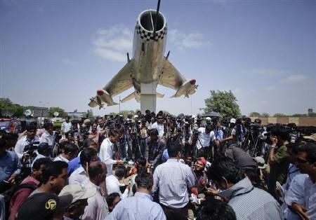 Media gather at the gates of the Mehran naval aviation base after troops ended operations against militants in Karachi May 23, 2011. REUTERS/Akhtar Soomro