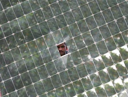 A worker looks through a solar concentrator panel (solar parabolic dish) at the Gadhia solar energy systems manufacturing unit at Gundlav village, about 400 km (250 miles) south of the western Indian city of Ahmedabad, December 16, 2009. REUTERS/Amit Dave