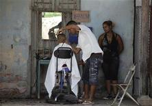 <p>A private-licensed barber cuts a boy's hair in Havana May 19, 2011. REUTERS/Desmond Boylan</p>
