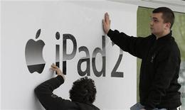 <p>Рабочие наклеивают плакат iPad 2 в магазине в Берлине, 25 марта 2011 года. Продажи планшетов iPad2 от Apple начнутся в России 27 мая с 19.00 МСК одновременно в крупных розничных сетях электроники Re:Store, М.Видео, Media Markt, Эльдорадо и Техносила, сообщили Рейтер представители компаний. REUTERS/Tobias Schwarz</p>