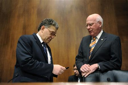 (L-R) Subcommittee Chairman Al Franken (D-MN) looks at his mobile phone as he and Committee Chairman Patrick Leahy (D-VT) arrive for a Senate Judiciary Committee hearing titled ''Protecting Mobile Privacy: Your Smartphones, Tablets, Cell Phones and Your Privacy'' on Capitol Hill in Washington May 10, 2011. REUTERS/Jonathan Ernst