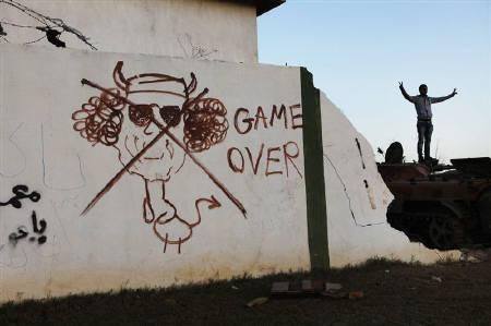 A caricature of Muammar Gaddafi is painted on the wall of the garrison headquarters in the rebel stronghold of Benghazi March 11, 2011.  REUTERS/Finbarr O'Reilly/Files
