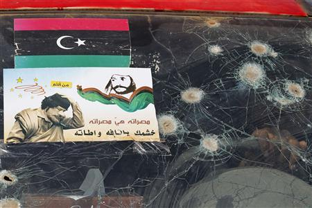 Bullet marks and a poster showing a defaced Muammar Gaddafi are seen on a Libyan rebel fighter's car in the eastern outskirts of Misrata, May 25, 2011. REUTERS/Zohra Bensemra