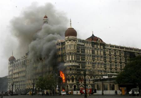 The Taj Mahal hotel is seen engulfed in smoke during a gun battle in Mumbai November 29, 2008.  REUTERS/Arko Datta/Files
