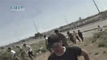 People run as gunfire is heard on the main highway in Homs, in this still image taken from video uploaded on a social media website, May 21, 2011. REUTERS/Social Media Website via Reuters TV