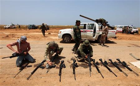 Rebel fighters clean their weapons before training in Giminis May 26, 2011. REUTERS/Mohammed Salem
