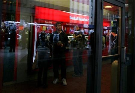 A customer at a Bank of America ATM watches protesters walk through New York's financial district, during a rally against government bailouts April 3, 2009. REUTERS/Brendan McDermid