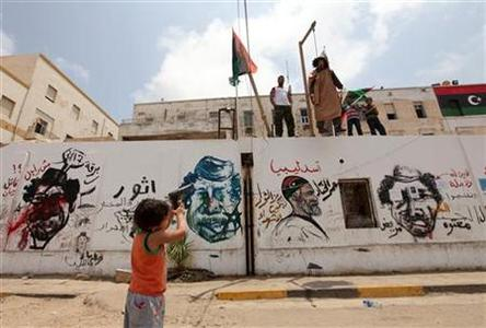 A Libyan boy points a toy gun to the effigy of Libyan leader Muammar Gaddafi during Friday prayers near the courthouse in Benghazi May 27, 2011. REUTERS/Mohammed Salem